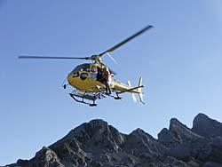 Grupo de rescate con el helicóptero de salvamento que acude a la zona de Picos de Europa para un traslado sanitario urgente.