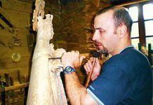 José Mª García Bouza, artesano de la madera, con una talla religiosa
