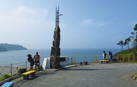 Monumento al Emigrante, al fondo la playa de Navia.