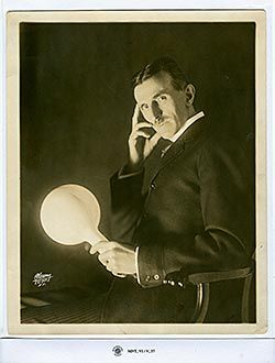 Tesla sostiene una lámpara inalámbrica llena de gas y recubierta de fósforo que desarrolló en 1890, medio siglo antes de que la luz fluorescente se comercializara.