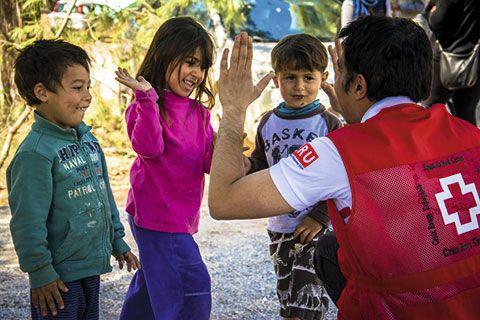Miembros de la Cruz Roja con niños refugiados