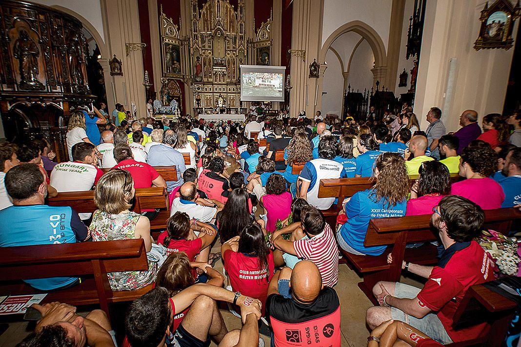 Retransmisión del Descenso a Nado de la Ría de Navia en una iglesia de localidad
