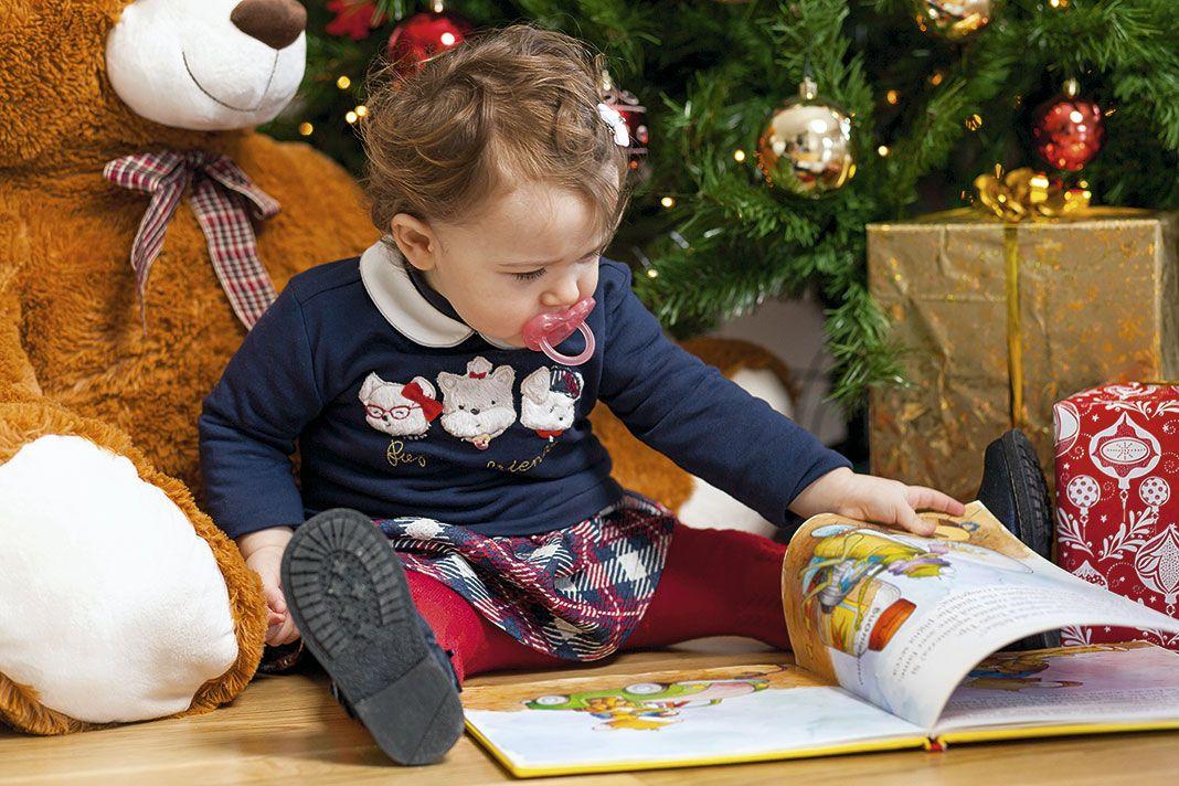 niña con un cuento en navidad
