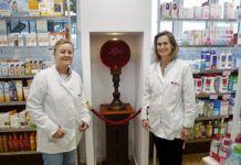 Silvia (izda.) y Nuria Campoamor (dcha.) junto a la bola de cristal que en el siglo XIX se ponía en el escaparate para indicar que el local era una farmacia