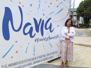Julia María López frente al cartel de la campaña de apoyo al comercio