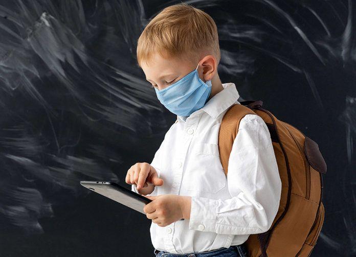 Niño en la escuela con mascarilla y tablet