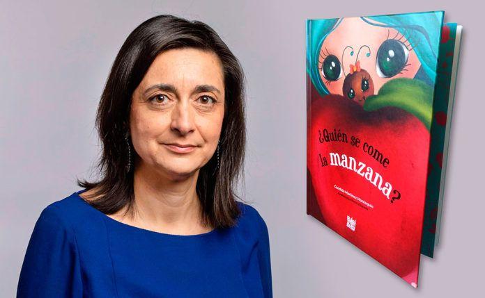 Cándida Martínez Montequín junto a la portada de su cuento ¿Quién se come la manzana?