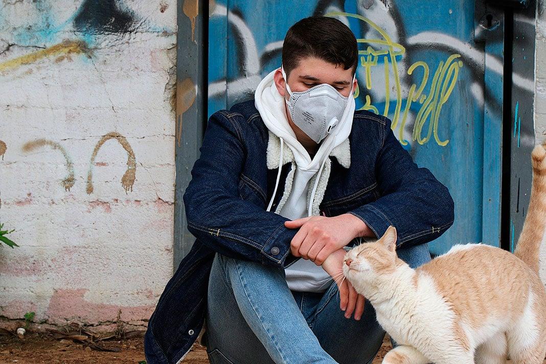 Chico con mascarilla acariciando un gato