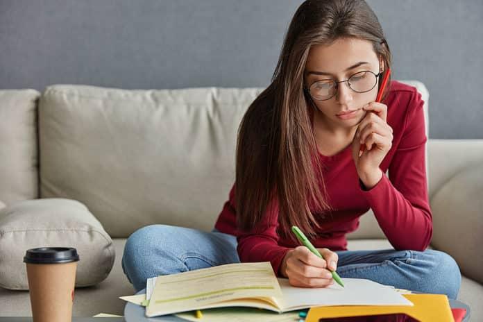 Chica joven escribiendo su curriculum vitae