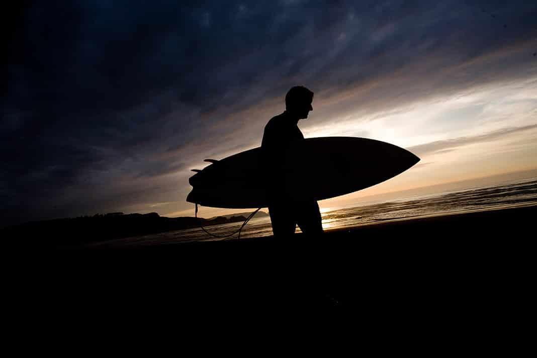 Un surfista al atardecer en la playa de Salinas