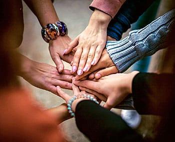 Grupo de personas unen sus manos